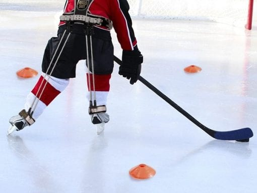 Young child playing ice hockey on a pond