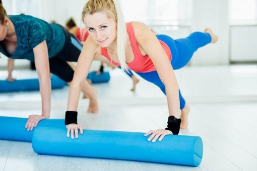 Sport and lifestyle concept. Slim fitness young girls with foam roller doing planking exercise indoors at home gymnastics.