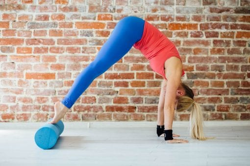 Young sporty women doing pilates exercises with foam roller in fitness studio. Sport, fitness, lifestyle and peiople comcept.
